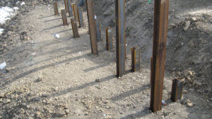 Steel piles driven into massena bridge construction ground.