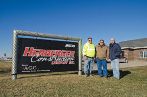 Two generations of Herberger mens tand by the Herberger Construction sign in Indianola, IA.