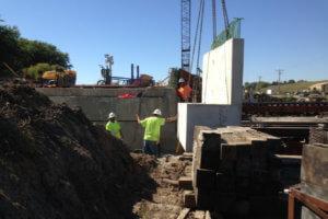Crew members work along concrete slabs.