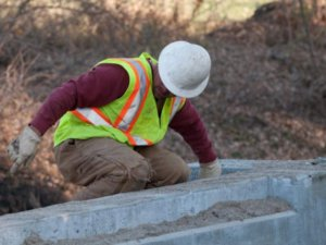 A worker kneels down to inspect concrete work.