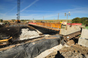 The new bridge is constructed, with materials laying in preparation.