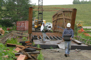 Workers walk along the site for the Cedar Bridge rebuild.
