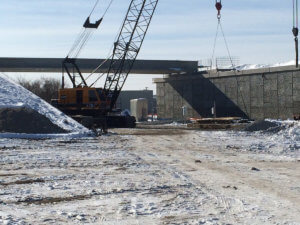 A crane prepares to lift materials above the Middle River stone.