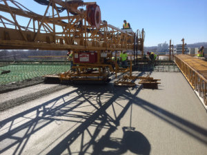 Concrete finishing is performed on the Middle River bridge.