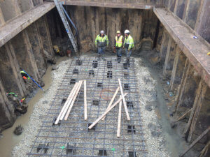 The crew smiles inside the foundational infrastructure of Middle River bridge.