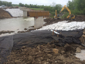 Construction crews work among tarps and rock on the Middle River bridge.
