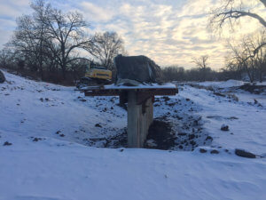 Snow sits on top of a bridge support.