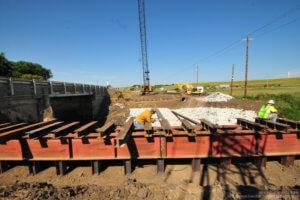 Crew members work on the beams of the Massena bridge.