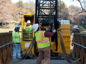 Project crew members utilize a crane in the construction project.