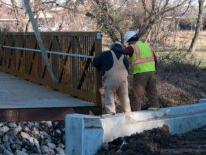 Herberger crew members inspect the Walker Johnston Park bridge.