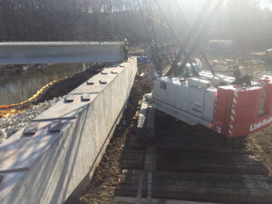 Cranes carefully place beams across the North River bridge.