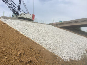 Gravel is laid on the incline beneath the bridge.
